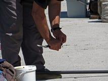 Personenfischer, der einen Fisch loshakt es mit den Händen fängt Lizenzfreies Stockfoto