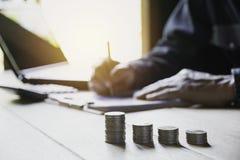 Personenfunktion und -schreiben auf Notizbuch mit Stapel Münzen für Finanz- und Bilanzauffassung lizenzfreie stockfotos