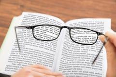 Personenhand, die Gläser mit Buch hält stockfoto