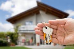 Personenhand, die Hausschlüssel hält lizenzfreies stockbild