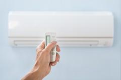 Personenhand, die Klimaanlage entfernt hält Lizenzfreies Stockfoto