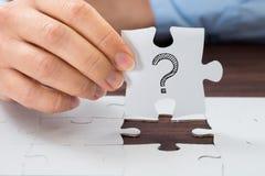 Personenhand, die Puzzlespiel mit Fragezeichen hält Lizenzfreie Stockbilder