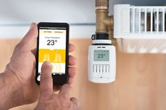 Personenhand, die Temperatur des Thermostats unter Verwendung des Mobiltelefons justiert Lizenzfreies Stockfoto