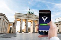 Personenhand mit Handy an Brandenburger Tor lizenzfreies stockbild