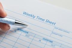 Personenhand mit Stift über wöchentlichem Stundenzettel Lizenzfreies Stockfoto