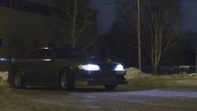 Personenkraftwagen, der auf einer schneebedeckten Straße in der Stadtstraße nachts, gefährliches Rennen treibt t?tigkeit Ein Auto stockfoto