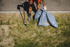 Personenreinigungspark mit einem Abfallgrabscher stockfotografie