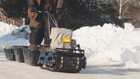 Personenvervoer op kruippakje minisneeuwscooter met een aanhangwagen en een passagier op een de winterweg royalty-vrije stock fotografie