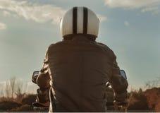 Personenvervoermotor met bruine leerjasje en helm stock foto