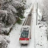 Personenzug, der entlang Schneespur sich bewegt Lizenzfreies Stockbild