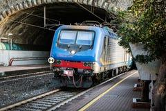 Personenzug, der vom Tunnel nahe Riomaggiore-Stadt, Cinque Terre, Italien verjagt Stockfotos