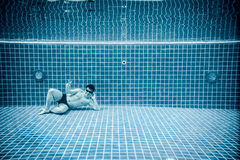 Personer ligger under vatten i en simbassäng Arkivfoton