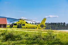 Personer med paramedicinsk utbildning hjälper patienten in i ambulanshelikoptern arkivfoto