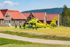 Personer med paramedicinsk utbildning hjälper patienten in i ambulanshelikoptern arkivbilder