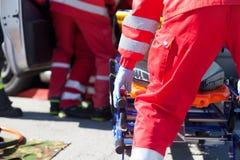 Personer med paramedicinsk utbildning i en räddningsaktion efter vägtrafikolycka royaltyfria bilder