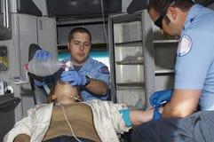 Personer med paramedicinsk utbildning med offret i ambulans Royaltyfri Foto