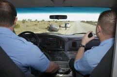 Personer med paramedicinsk utbildning som ankommer på den forcerade platsen för bil Arkivbild