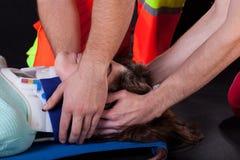Personer med paramedicinsk utbildning som använder den cervikala kragen Royaltyfri Fotografi