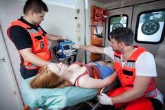 Personer med paramedicinsk utbildning som applicerar första hjälpen i ambulans Royaltyfria Bilder