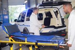 Personer med paramedicinsk utbildning som förbereder ambulansen arkivfoton