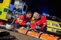 Personer med paramedicinsk utbildning som ger firstaid till mopedchauffören Royaltyfri Fotografi