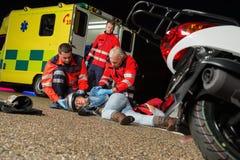 Personer med paramedicinsk utbildning som hjälper den sårade motorcykelchauffören Arkivbilder
