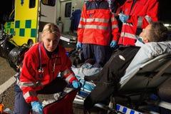 Personer med paramedicinsk utbildning som hjälper den sårade motorcykelmanchauffören Royaltyfri Bild