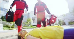 Personer med paramedicinsk utbildning som kör in mot sårad flicka lager videofilmer