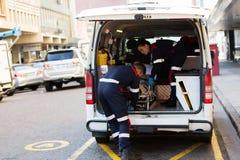 Personer med paramedicinsk utbildning som offloading patienten Royaltyfri Fotografi