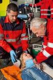 Personer med paramedicinsk utbildning som tar bort hjälmen från motorcykelchauffören Royaltyfria Bilder