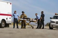 Personer med paramedicinsk utbildning som transporterar offret på båren Royaltyfri Fotografi