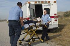 Personer med paramedicinsk utbildning som transporterar offret på båren Arkivbild