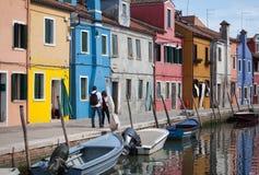 2 personer som går - hus av Burano och reflexionen i vattnet Vattenvägar med traditionella fartyg och den färgrika fasaden Venedi fotografering för bildbyråer
