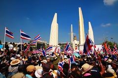 Personer som protesterar lyfter thailändska flaggor på demokratimonumentet Arkivfoto