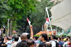 Personer som protesterar vinkar flaggor på den Maj dagen samlar Singapore Royaltyfri Foto