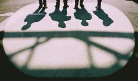 4 personerskuggor på jordningen Royaltyfri Foto