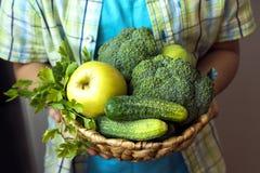 Personhållkorg med gröna grönsaker arkivbild
