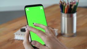 Personhålltelefon med grön skärmskärm i hand arkivfilmer