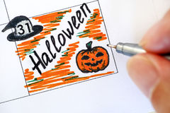 Personhand med allhelgonaafton för pennhandstilpåminnelse i kalender Arkivfoto