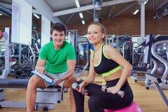 Personlig instruktör och en kvinna som kopplar av i idrottshallen efter övning arkivbild