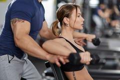 Personlig instruktör som hjälper den unga kvinnan i idrottshallen Royaltyfri Fotografi