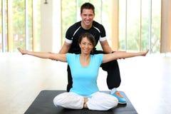 Personlig instruktör som instruerar kvinnan i gymnastik arkivfoto