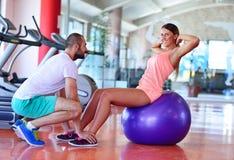 Personlig instruktör som utbildar en kvinna i idrottshallen med yogabollen Arkivfoton