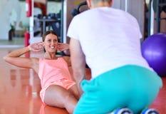 Personlig instruktör som utbildar en kvinna i idrottshallen med yogabollen Arkivfoto