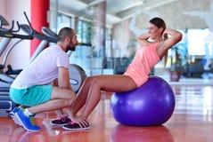 Personlig instruktör som utbildar en kvinna i idrottshallen med yogabollen Royaltyfria Foton