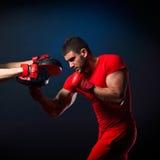 Personlig instruktörmanlagledare och man som övar boxning Arkivbild