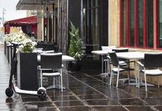 Personlig mobilty elektrisk sparkcykel som parkeras av det öde trottoarkafét på snöig röd & svart klippning för dag - arkivbilder