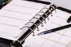 Personlig organisatör eller stadsplanerare med pennan på vit bakgrund Fotografering för Bildbyråer