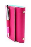 Personlig organisatör i rosa färgfärg med kulspetspennan på vit bakgrund Fotografering för Bildbyråer