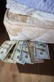 Personliga besparingar i dolars under madrassen Arkivbild